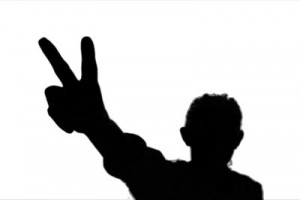 stock-footage-young-adult-woman-makes-victory-sign-against-green-screen-chroma-background-back-lit-silhouette