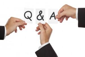 Business men's hand holding cards forming Q&A